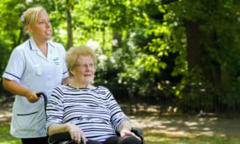 Better healthcare carer pushing elderly woman in a wheelchair outdoors