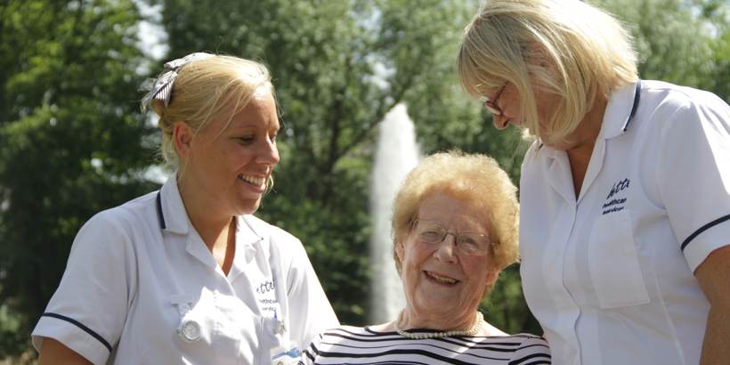 Elderly lady and two uniformed care assistants in a garden smiling