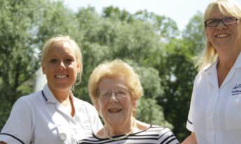 Two Better Healthcare nurses standing on either side of an elderly woman in a wheelchair