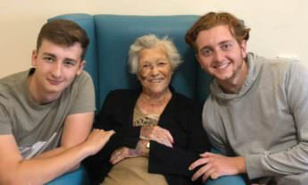 Two young men with elderly woman smiling