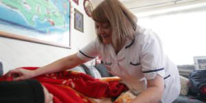 Nurse-covering-patient-with-blanket