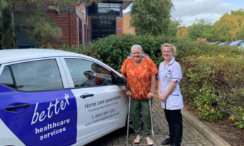 BHC carer with patient beside the BHC company car